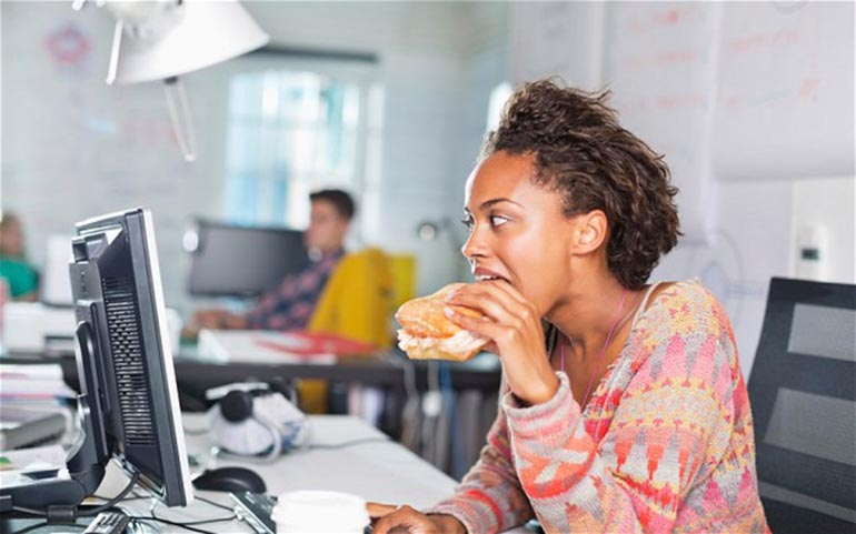 Young Black Woman Eating at Her Desk